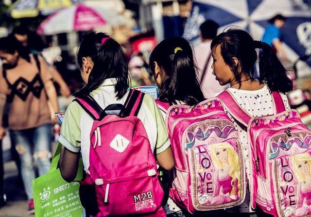 实拍背着书包上学的小学生,书包大如行李,多数家长帮背着