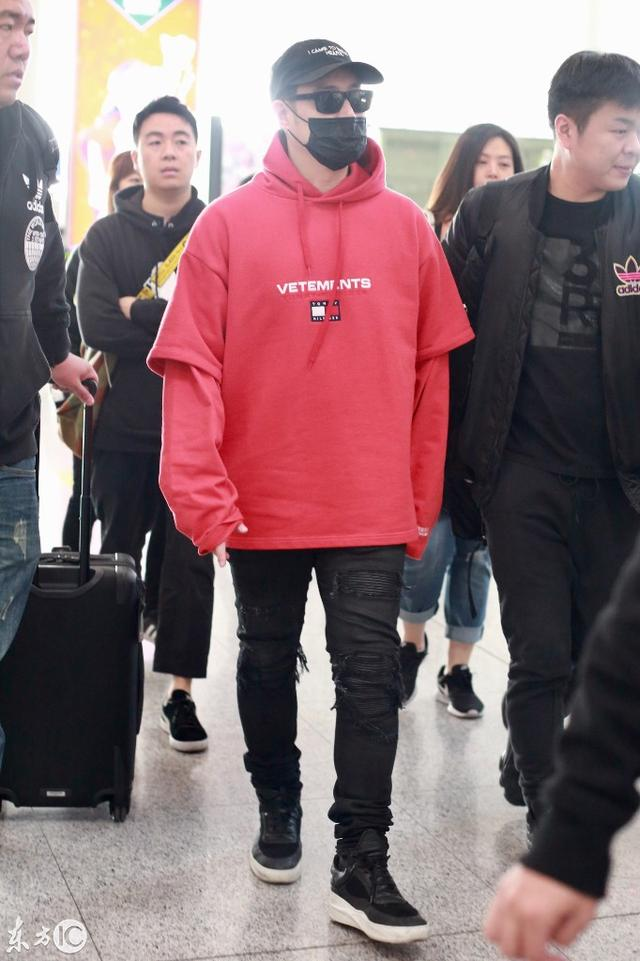 潘玮柏现身机场红色连帽卫衣  下身穿黑色破洞休闲裤