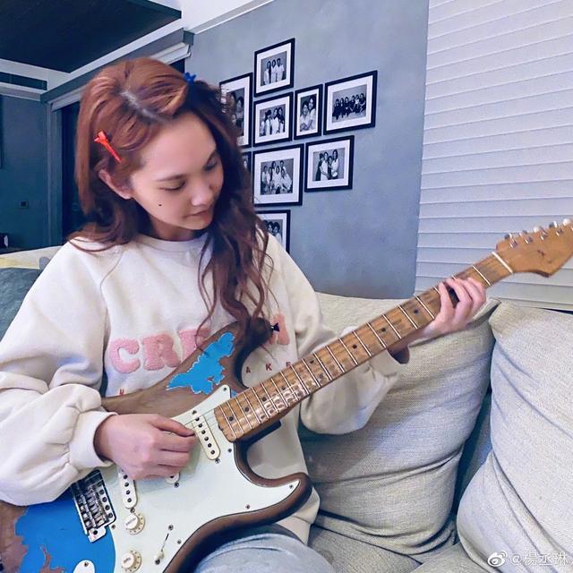 杨丞琳把玩吉他表情呆萌 穿白色卫衣出镜卷发迷人