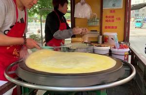 夫妻俩卖东北大煎饼,5元一套,刮风下雨天天出摊,已经10几年了