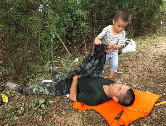 武警抗洪官兵马路边倒头睡着 路过男童拿起外套盖身上