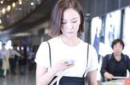 王珞丹穿白色T恤搭闊腿褲休閑簡單,手拿帽子一直玩手機很繁忙