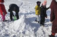 东北下了一夜的暴雪,大人领着小孩堆起了雪人,看着好温馨啊