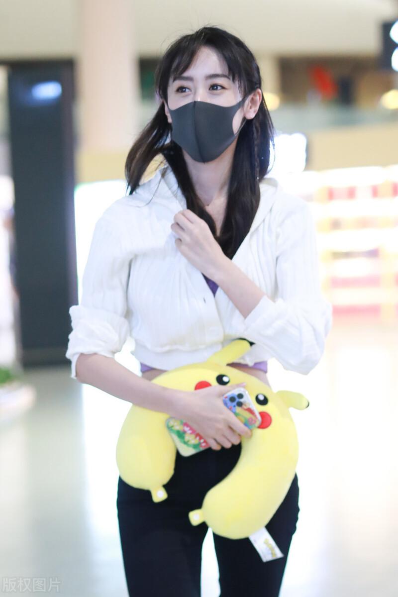袁冰妍穿白色短款针织衫现身机场,手拿皮卡丘颈椎萌妹子一枚