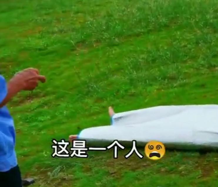 江西一男子裹白袋躺草地追剧,只露双脚吓得路人急喊保安,男子:这样比较凉快