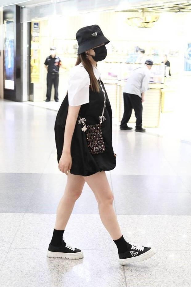 怀孕的麦迪娜仍不算胖,叠穿吊带裙走机场打扮甜美,细腿真抢镜