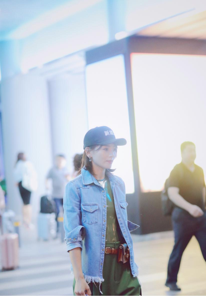 刘涛穿牛仔外套配绿色工装裤,时尚造型现机场,手拎车轮包成亮点